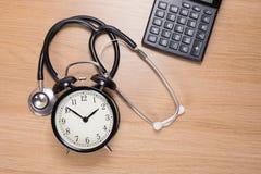 Stetoskop wśród budzika z kalkulatorem zdjęcia royalty free