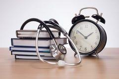 Stetoskop wśród stosu planiści i zegar zdjęcia royalty free