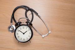 Stetoskop z budzika lying on the beach na drewnianym biurku obrazy stock