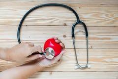 Stetoskop z Czerwonym kierowym kształtem na drewnianym tle Opieki zdrowotnej i ubezpieczenia pojęcie zdjęcia stock