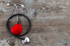 Stetoskop z czerwonym sercem na drewnianym tle z kopii przestrzenią, Obrazy Stock