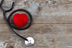 Stetoskop z czerwonym sercem na drewnianym tle z kopii przestrzenią, Zdjęcia Royalty Free