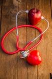Stetoskop z czerwonymi jabłkami na drewnianym tle Obraz Stock