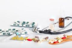 Stetoskop z różnorodnymi medycynami, pigułkami, ampules i strzykawkami, Fotografia Stock