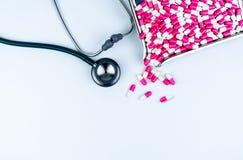 Stetoskop z stosem antybiotyczne kapsuł pigułki na stal nierdzewna leka tacy Antybiotycznego leka opór i overuse medyczny zdjęcie stock