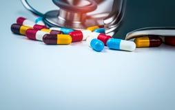 Stetoskop z stosem kolorowe antybiotyczne kapsuł pigułki na bielu stole z lek tacą Antimicrobial leka opór zdjęcia stock