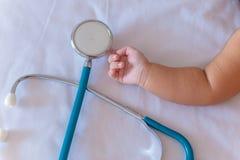 stetoskopet för medicinska instrument i hand av nyfött behandla som ett barn flickan Arkivfoto