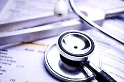 Stetoskopet och att trimma - dela sig på den medicinska referensboken Arkivfoto
