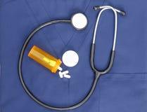 Stetoskopet skurar och Pills Fotografering för Bildbyråer