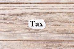 Steuer des Wortes auf Papier Konzept Wörter der Steuer auf einem hölzernen Hintergrund Lizenzfreie Stockfotos