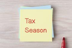 Steuer-Jahreszeit geschrieben auf Anmerkung stockbilder