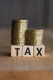 Steuer-Konzept mit Holzklotz auf Staplungsmünzen Lizenzfreie Stockfotografie