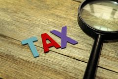 Steuer-Konzeptvergrößerungsglas und das bunte hölzerne Alphabet auf hölzernem Hintergrund stockbilder