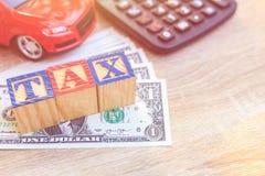 STEUER schreiben in hölzernen Kasten des Farbalphabetes auf US-Dollar und rotes Auto Stockfotos