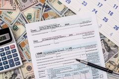 Steuer 1040 von mit US-Dollar Banknote, Stift Lizenzfreie Stockbilder