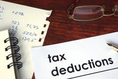 Steuerabzüge geschrieben auf ein Papier Lizenzfreies Stockfoto