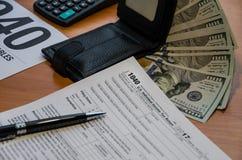 Steuerformular 1040, Geldbörse, Dollar, Taschenrechner und Stift auf dem Tisch stockfoto