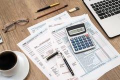 1040 Steuerformular, Laptop, Gläser, Kaffee Stockfoto