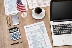 1040 Steuerformular, Laptop, Gläser, Kaffee Stockbilder