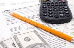 Steuerformular mit Bleistift-Bargeld und Taschenrechner Stockfotografie
