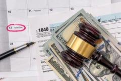 1040 Steuerformular mit Hammergeldstift und -taschenrechner Stockbild