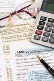Steuerformular mit Stift, Taschenrechner und Gläsern Lizenzfreie Stockbilder