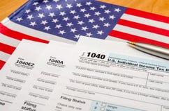 1040 Steuerformular mit Stift und Flagge Lizenzfreie Stockfotos