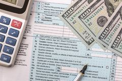 1040 Steuerformular mit Taschenrechner, Stift, Gläsern und Dollar Stockbild