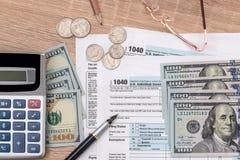 1040 Steuerformular mit Taschenrechner, Stift, Gläsern und Dollarbanknote Stockfotografie