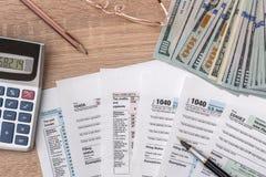 1040 Steuerformular mit Taschenrechner, Stift, Gläsern und Dollarbanknote Lizenzfreie Stockfotografie