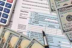 1040 Steuerformular mit Taschenrechner, Stift, Gläsern und Dollarbanknote; Lizenzfreie Stockfotos