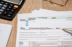 1040 Steuerformular mit Taschenrechner, Stift und Dollar Stockfotografie
