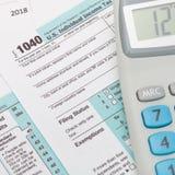 Steuerformular und Taschenrechner USA 1040 über ihm - nahe hohe Atelieraufnahme Lizenzfreie Stockfotografie
