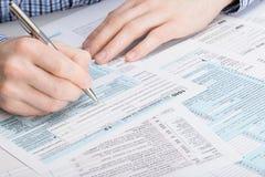 Steuerformular US 1040 - Mann, der Steuerformular ergänzt - Atelieraufnahme Stockfoto