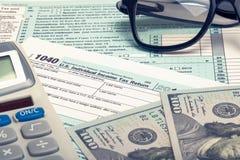 Steuerformular USA 1040, Taschenrechner, Gläser und Dollar - Atelieraufnahme Gefiltertes Bild: Kreuz verarbeiteter Weinleseeffekt Lizenzfreies Stockfoto