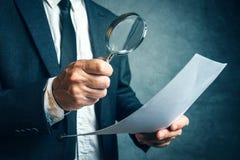 Steuerinspektor, der Finanzdokumente durch magnifyi nachforscht Lizenzfreie Stockfotografie