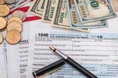 Steuerkonzept - 1040 Steuerformular, Stift, wir Geld Stockfotografie