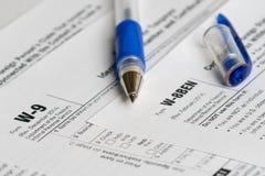 Steuermeldeformulare mit geöffnetem blauem Stift Stockbilder