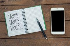 Steuern dreimal am Notizblock, am Bleistift und am intelligenten Telefon Stockbilder
