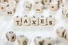 Steuern fassen geschrieben auf hölzernen Block ab Lizenzfreie Stockfotografie