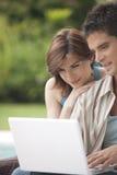 Steuern Sie die Technologie-Paare automatisch an, die Laptop im Garten betrachten Lizenzfreies Stockfoto