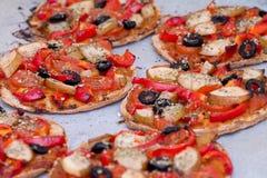 Steuern Sie gebackene Minipizza des strengen Vegetariers auf Pergamentpapier automatisch an Lizenzfreie Stockfotografie