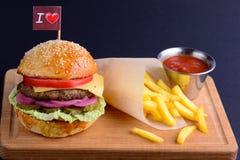 Steuern Sie gemachten Hamburger mit Rindfleisch, Zwiebel, Tomate, Kopfsalat und Käse automatisch an Frischer Burger auf einem sch Stockfoto