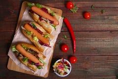 Steuern Sie hergestellten Hotdog - Sandwich mit Kopfsalat auf hölzernem Hintergrund automatisch an stockfotos
