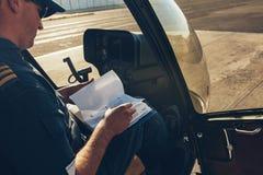 Steuern Sie innerhalb des Hubschraubers, der ein manuelles Buch liest lizenzfreie stockfotografie