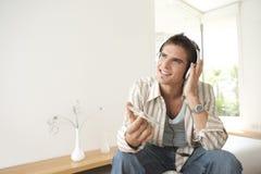 Steuern Sie Technologie-Mann-Holding-Kopfhörer automatisch an Stockfotografie