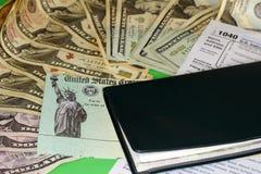 Steuerrückzahlungs-Kontrolle mit Geld und Scheckheft Stockfotografie