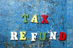 Steuerrückzahlungstext auf bunten hölzernen Buchstaben Holz-ABC am blauen Schmutzhintergrund Stockfotos