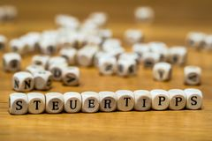 Steuertipps written with wooden cubes in German stock images