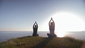 Steuerung geistig, junger Mann und Frau, die auf den Berg betrachtet das Meer an meditiert in Lotussitz sitzt stock footage